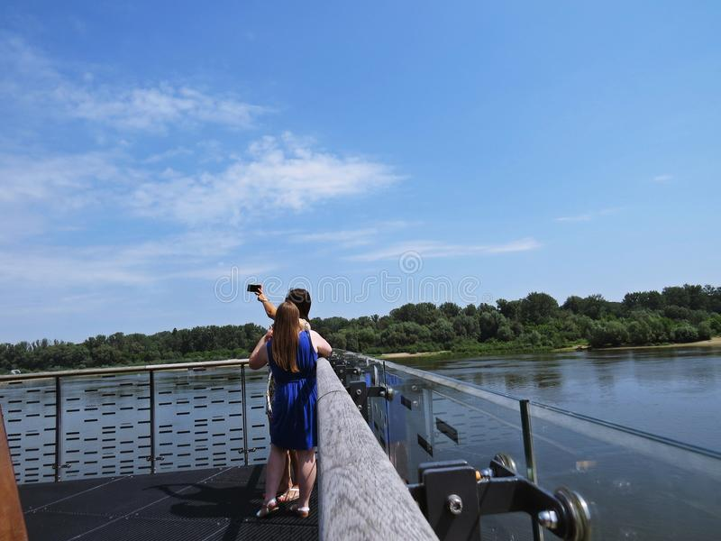 Two Girls Shooting Selfie Picture while Standing on a Viewing Platform over Vistula River in Warsaw, Poland stock photos