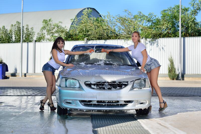 Two girls in shorts and t-shirt washes the car at the car wash stock image