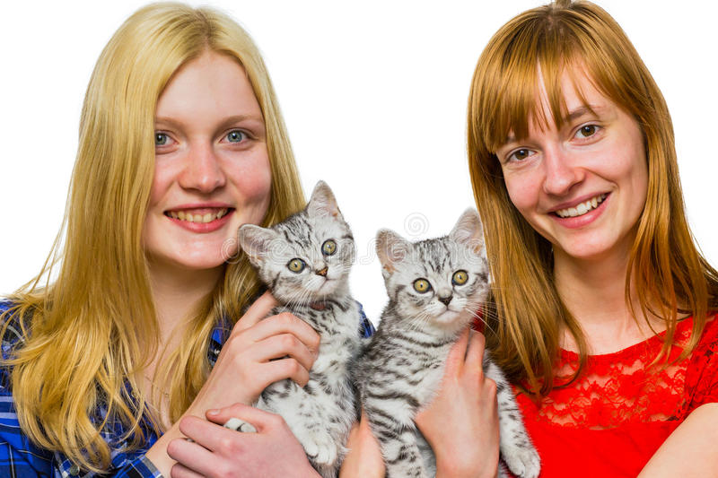 Two girls showing young silver tabby cats. Two caucasian teenage girls showing young british short hair black silver tabby spotted cats isolated on white stock photography