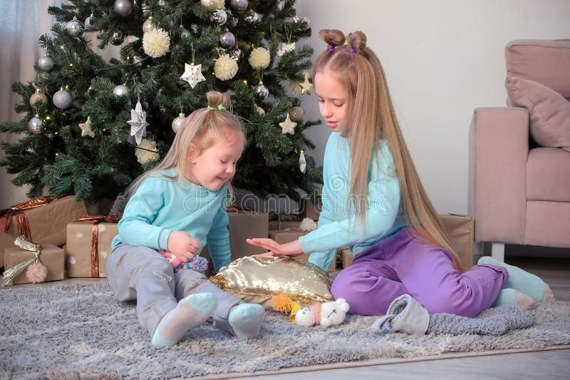 Two girls sisters draw fingers on pillow with sequins sit near Christmas tree. royalty free stock photos