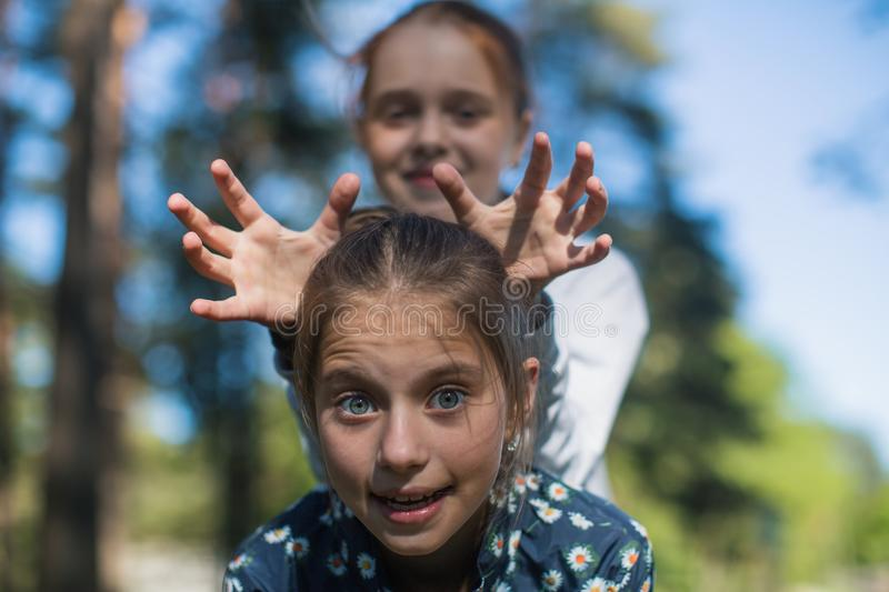 Two girls sisters or girlfriends having fun outdoors . stock photography