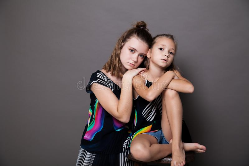 Two girls sisters side by side on a grey background. 1 stock photos