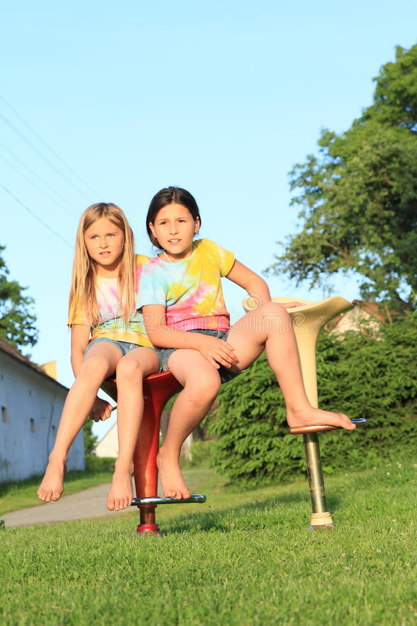Two girls sitting on bar chairs royalty free stock photos