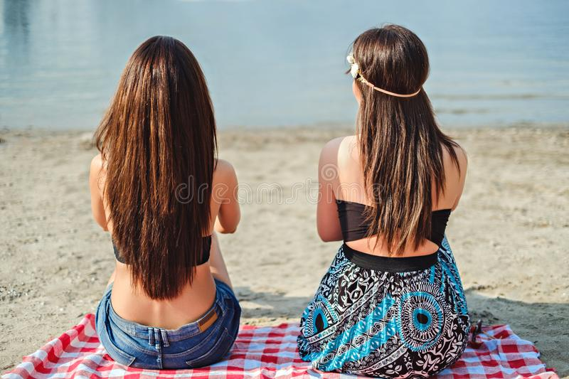 Two girls sitting on the beach and watching the sea royalty free stock photo