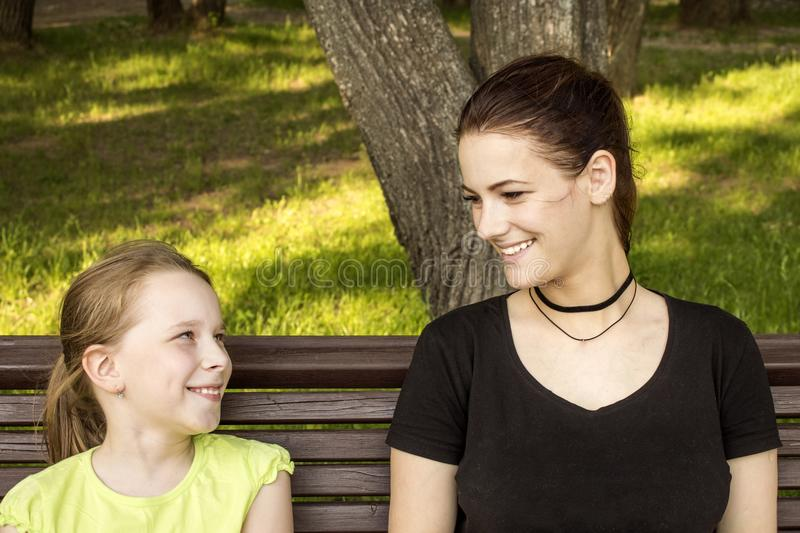 Two girls are sitting on a bench talking and laughing royalty free stock images