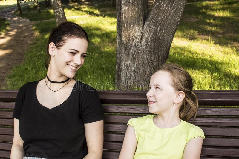 Two girls are sitting on a bench talking and laughing stock photo