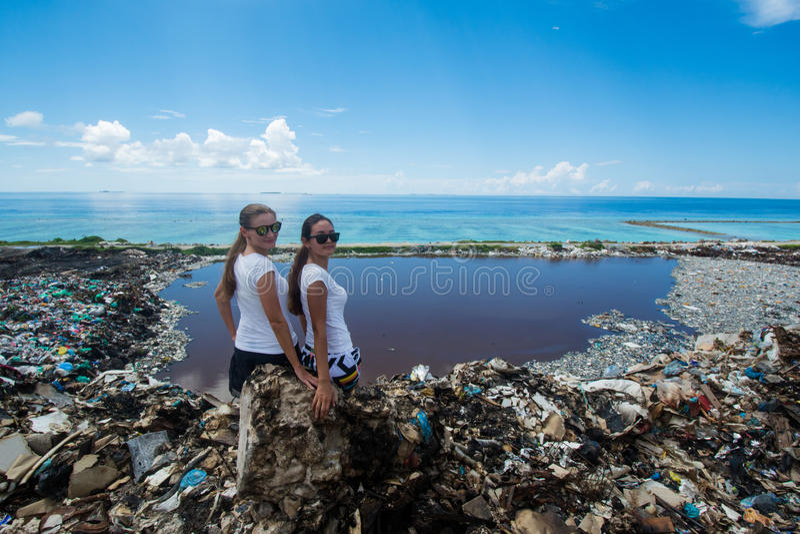 Two girls sitting on garbage mountain royalty free stock photography
