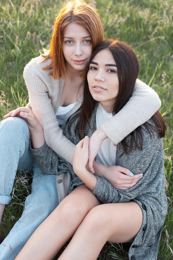Two cute girls sitting on the grass stock images