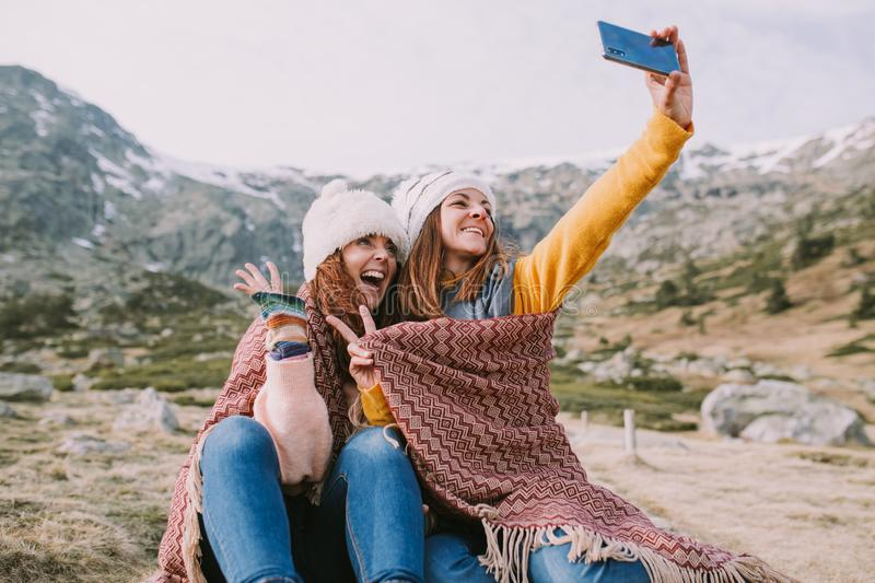 Two girls are sitting in the meadow and take a picture with their mobile stock photos