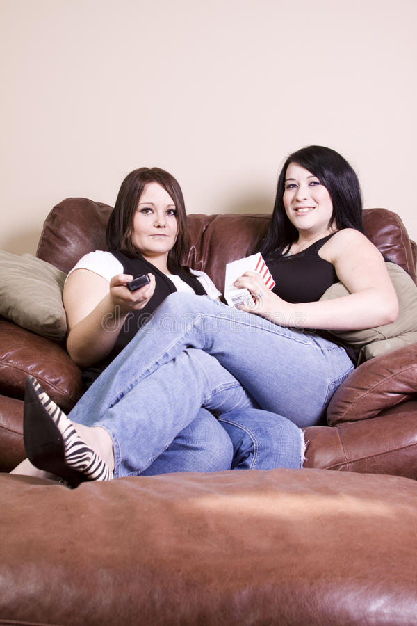 Download Two Girls Sitting On The Sofa Watching A Movie Stock Image - Image: 14055375
