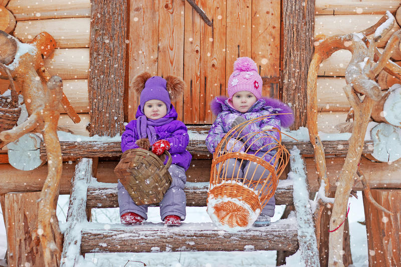 Two girls are sitting on the steps in winter royalty free stock photo