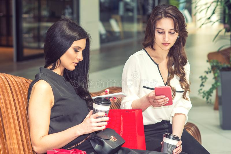 Two girls with smartphone and shopping bags sitting on bench in shopping mall royalty free stock photos
