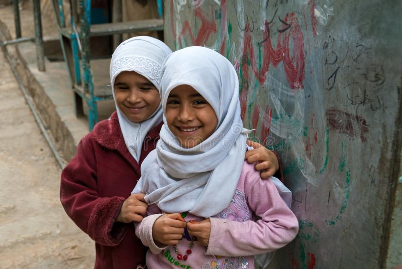 Girls in Yemen. Two girls smile at the camera outside their house on May 4, 2007 in Sanaa, Yemen. Children in Yemen are culturally and socially valued royalty free stock photos