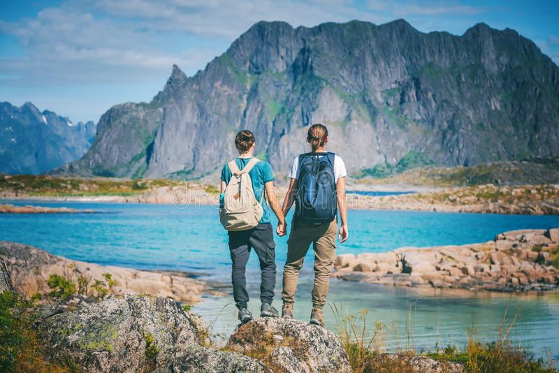 Two girls stand holding hands on the background of the Lofoten Islands, traveling to Norway, Scandinavia northern Europe royalty free stock photo