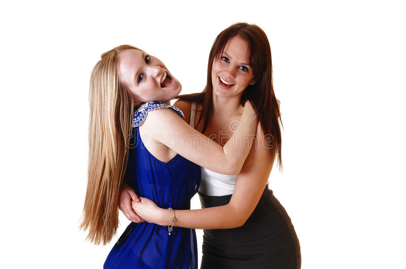 Two girls standing. Two beautiful young women standing in the studio pushing there out, one blond and the other one brunette in short dresses, over white stock photography