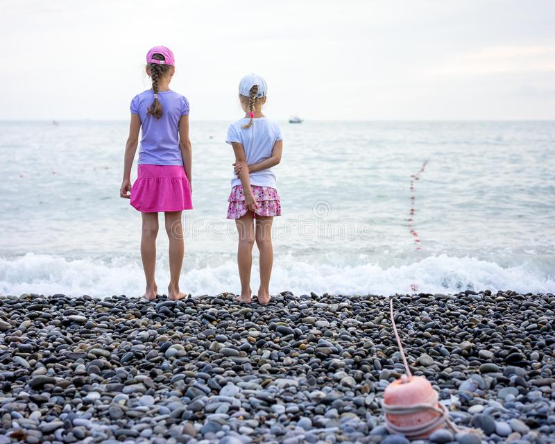Two girls standing on shore of the sea royalty free stock images