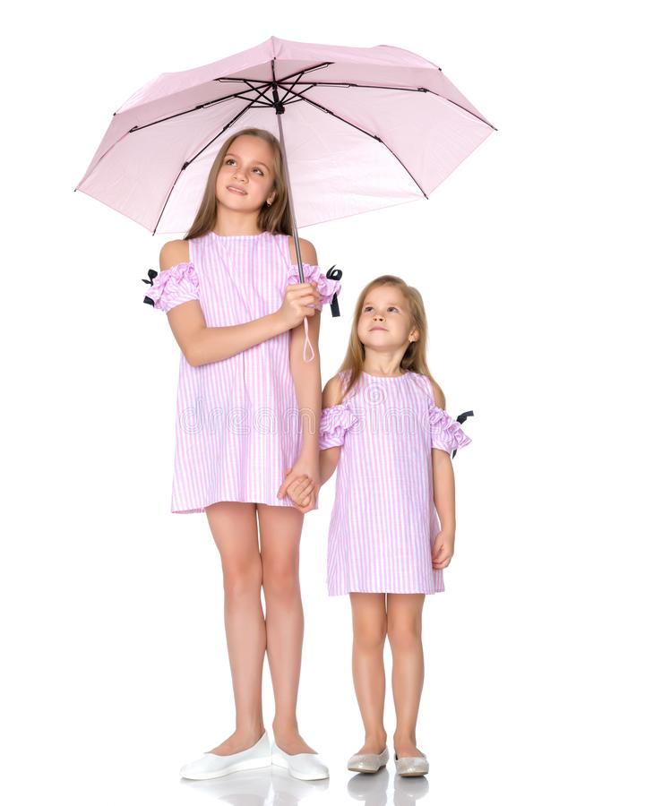 Two girls are standing under umbrellas. royalty free stock image