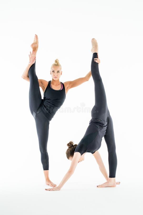 Two girls stretch stock photos