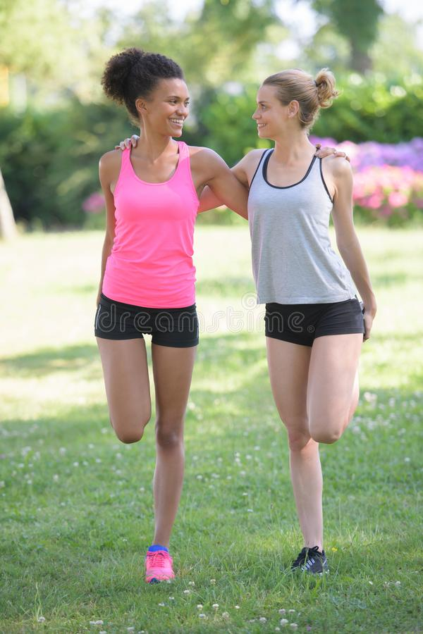 Two girls stretching leg muscles outdoors in park royalty free stock photography