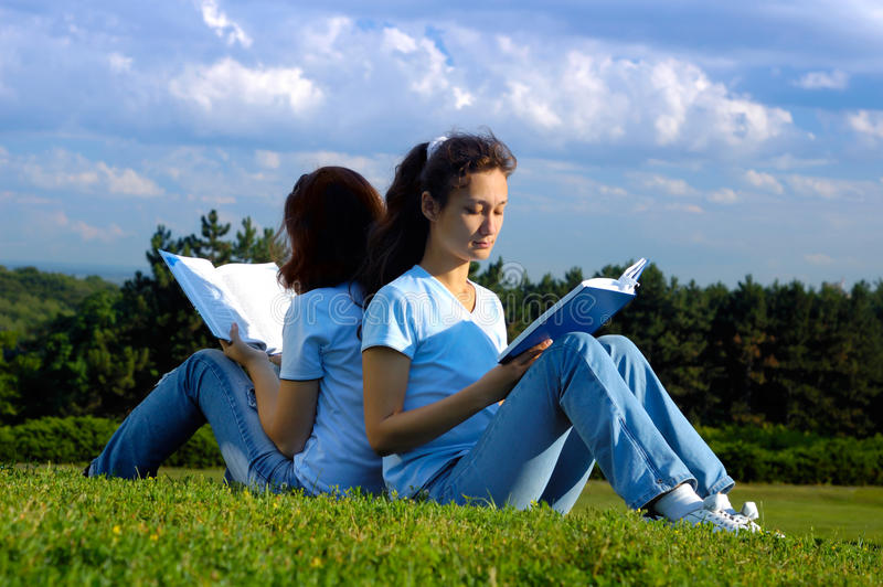 Two girls students studying reading outdoors. Two girls sitting on grass studying in the nature reading books outside royalty free stock image