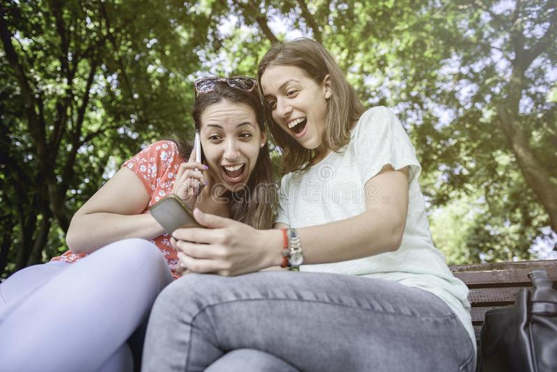 Two girls surprise social media unexpected youth millennial friendship media concept addiction to new technology trends lifestyle stock photography