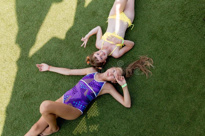 Two girls in swimsuit are having fun on the grass by the pool royalty free stock image