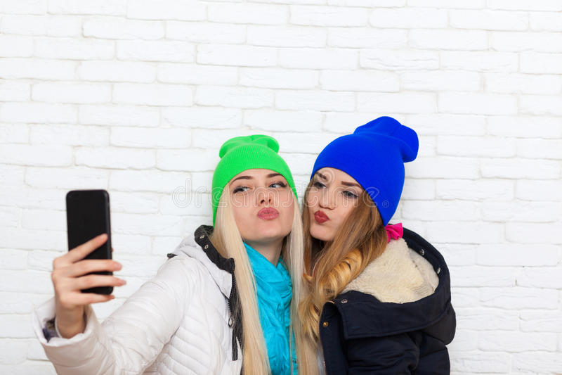 Two girls taking selfie picture with duck face lips emotion women friends posing smart phone photo royalty free stock images