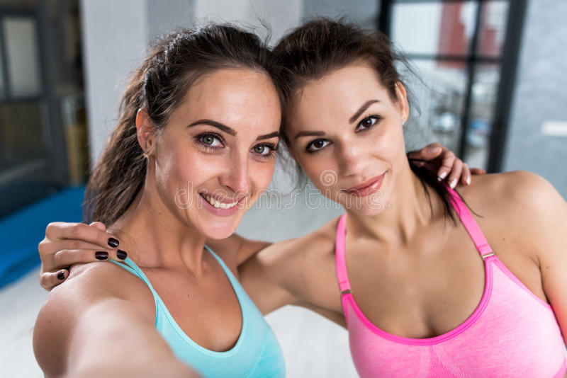Two girls taking selfie wearing sports bra indoors. Close-up shot of female athletes smiling at camera hugging each stock photography