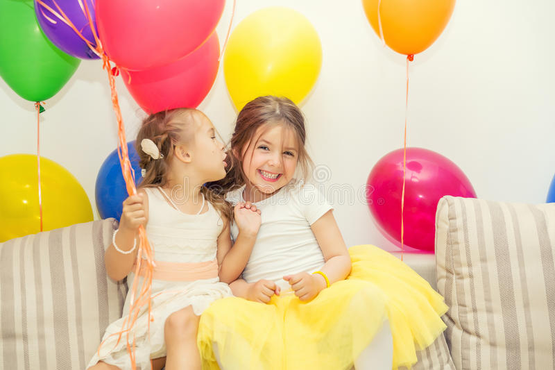 Two girls talking at birthday party. Two little girls talking at a birthday party royalty free stock photography