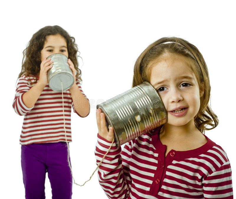 Two girls talking on a tin phone. Isolated on white royalty free stock images