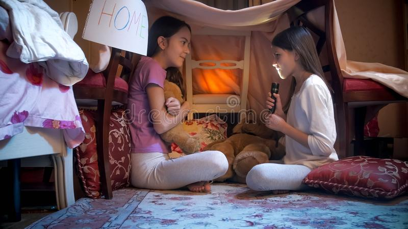 Two girls in pajamas telling stories with flashlight in selfmade tent stock photos
