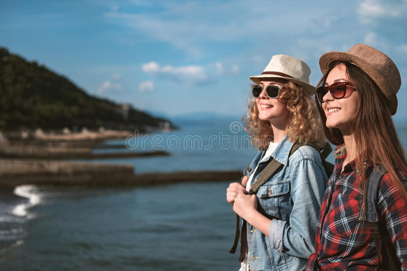 Two girls are traveling along the seashore royalty free stock photography