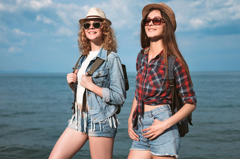 Two girls are traveling along the seashore royalty free stock photo