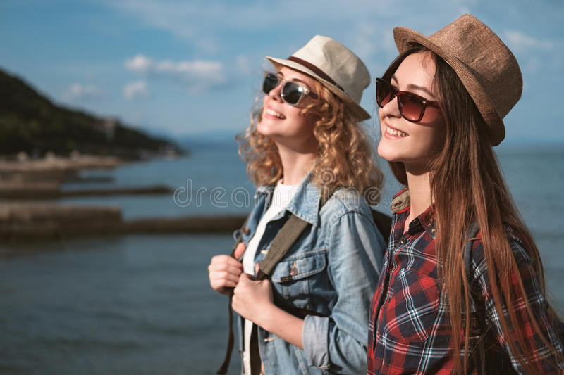Two girls are traveling along the seashore stock images