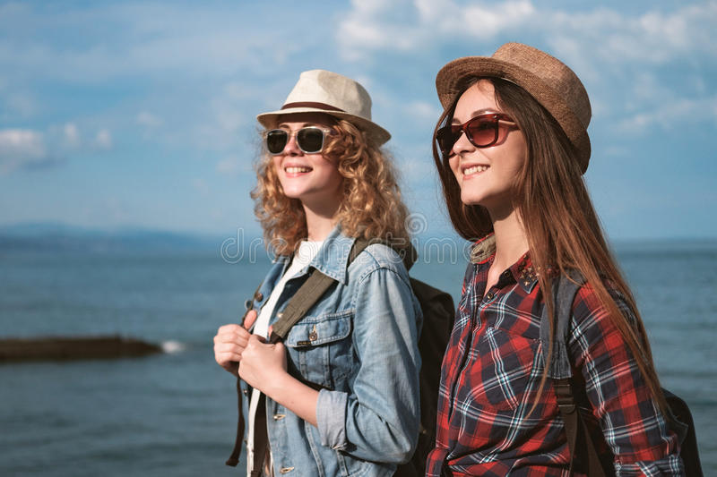 Two girls are traveling along the seashore royalty free stock image