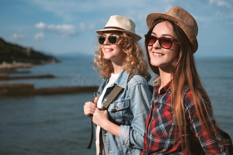 Two girls are traveling along the seashore royalty free stock photos