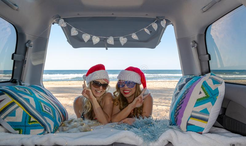 Two girls traveling celebrate Christmas by the beach in summer royalty free stock images
