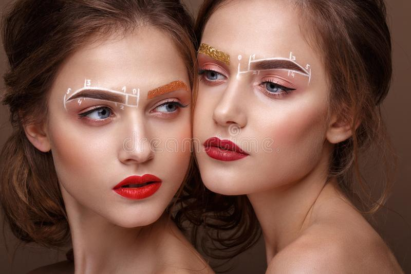 Two girls are twin sisters with an unusual eyebrow makeup. Beauty face. stock photography