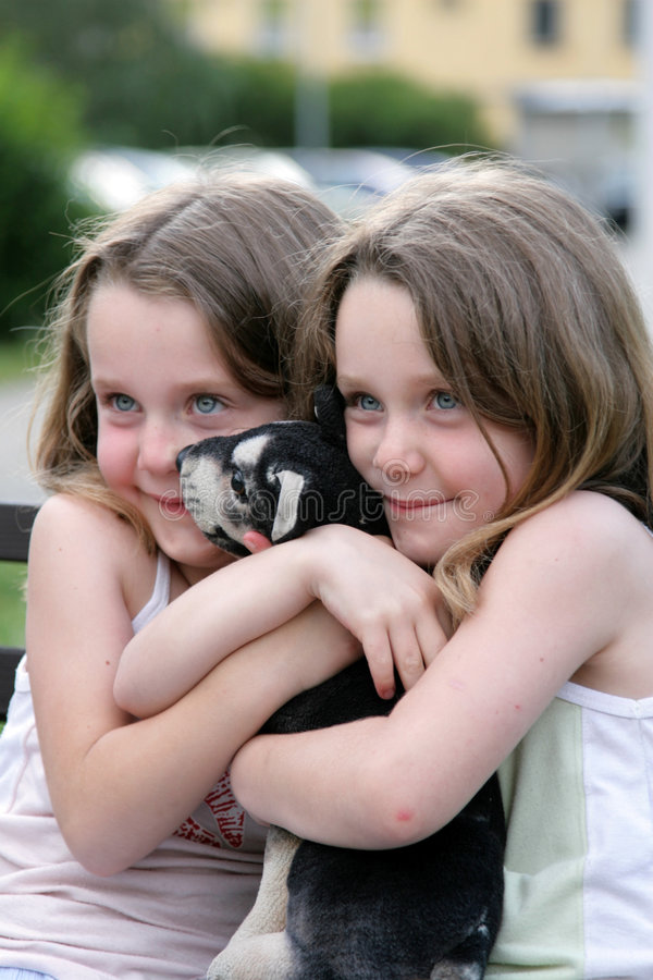 Two girls - twins. With dog on the street royalty free stock images