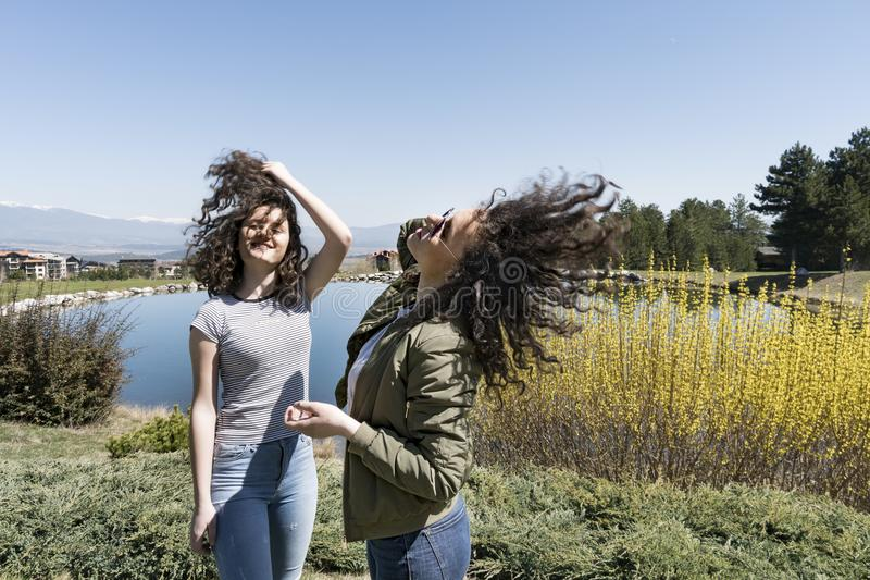 Two girls twins holding curly hair waved by wind royalty free stock photos