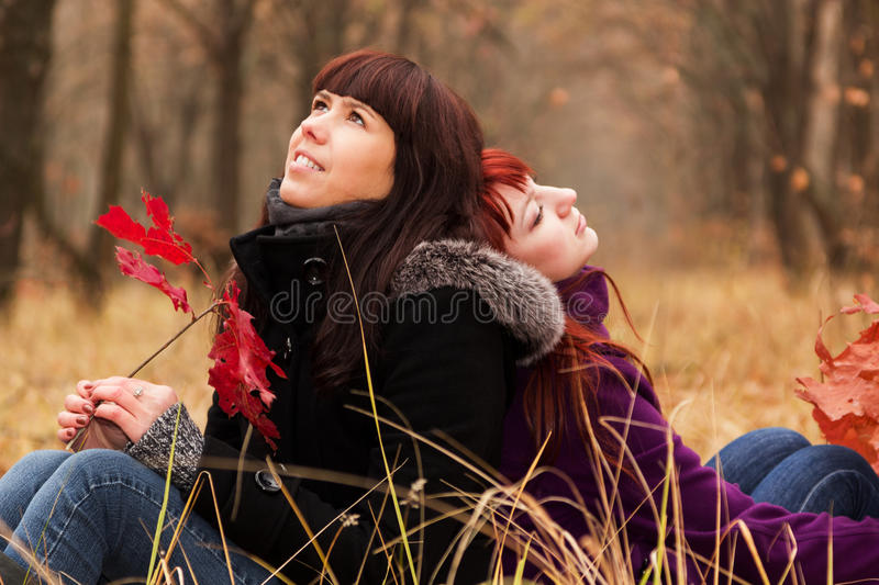 Two girls twins in the park stock images
