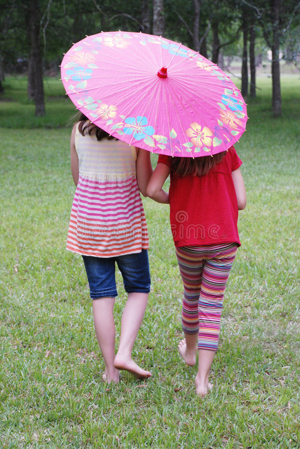 Two Girls with an Umbrella. Two girls walking together with an umbrella outdoors at the park stock photo