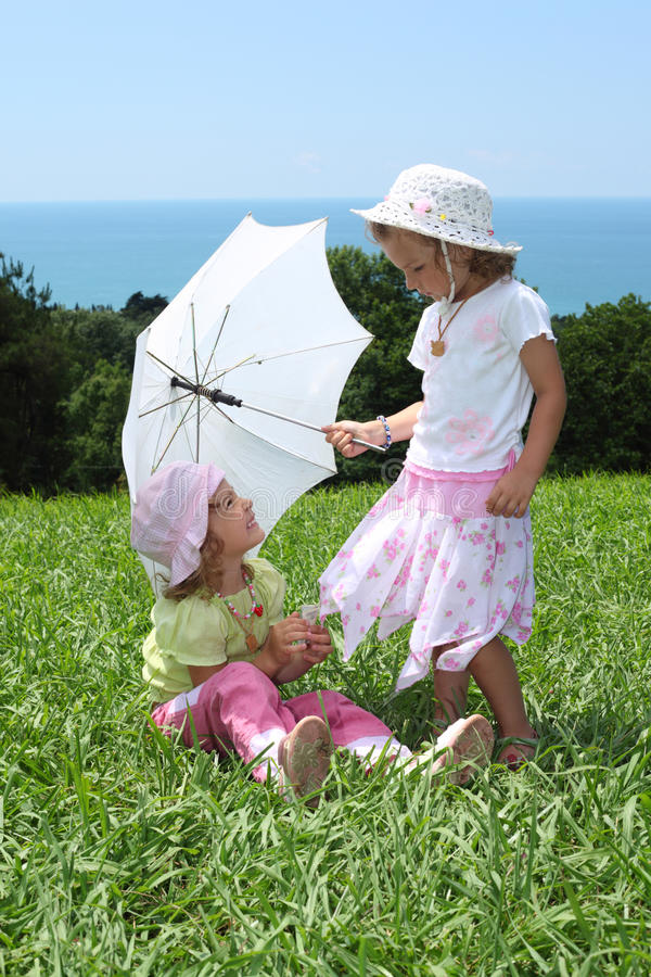 Two Girls With An Umbrella On Lawn Royalty Free Stock Photos