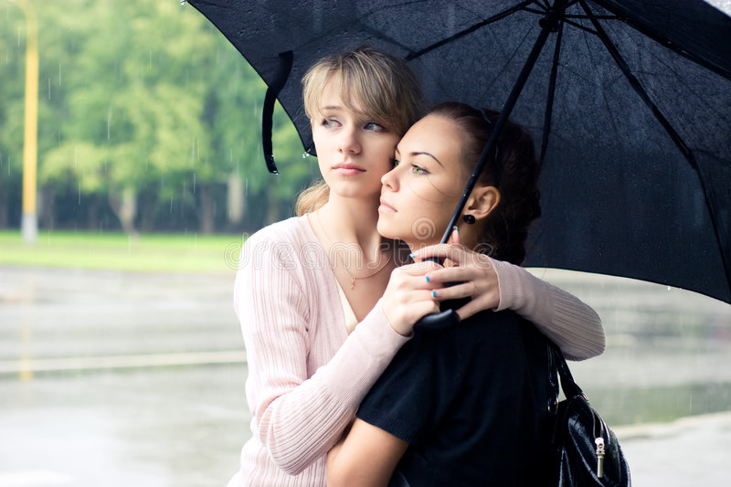 Two girls under umbrella royalty free stock photography