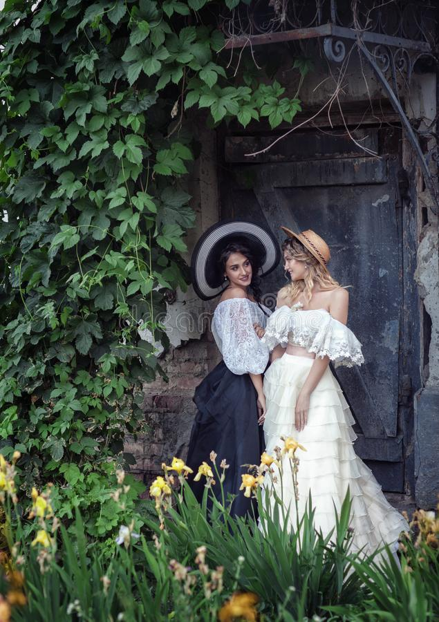 Two girls in vintage clothes and hats royalty free stock photos