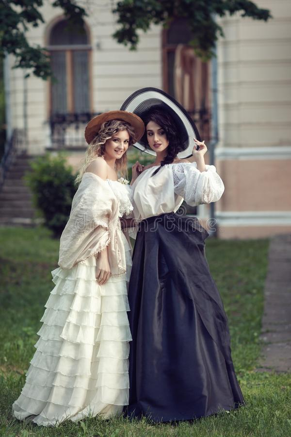 Two girls in vintage clothes and hats stock images