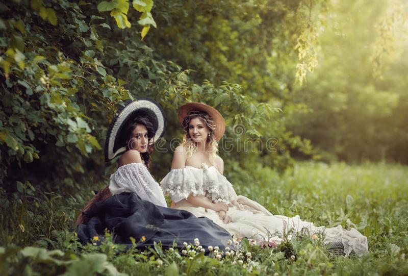 Two girls in vintage clothes and hats royalty free stock images