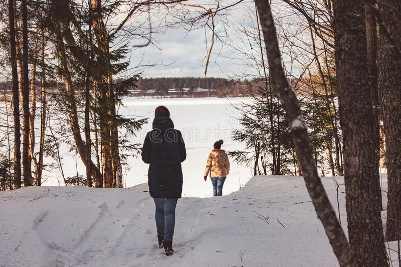Two girls walk through the winter forest to the lake royalty free stock images