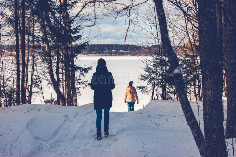 Two girls walk through the winter forest to the lake stock photo