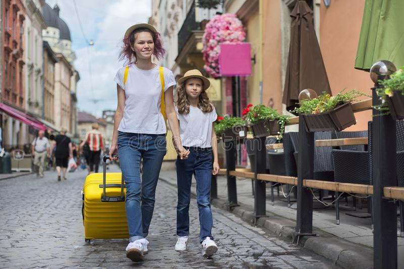 Two girls walking in tourist city holding hands with yellow suitcase royalty free stock photo